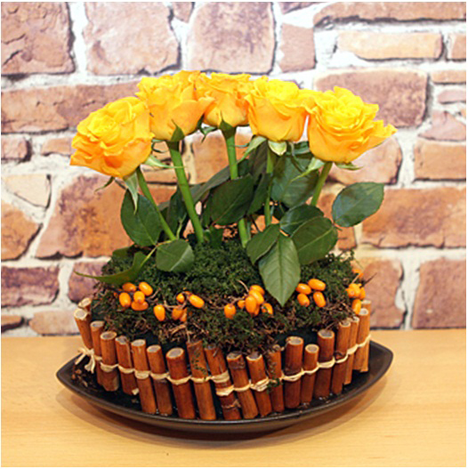 diy flower arrangement yellow roses bamboo stalks rosehips moss