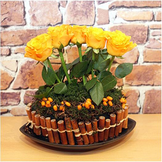 diy flower arrangement yellow roses bamboo stalks rosehips moss