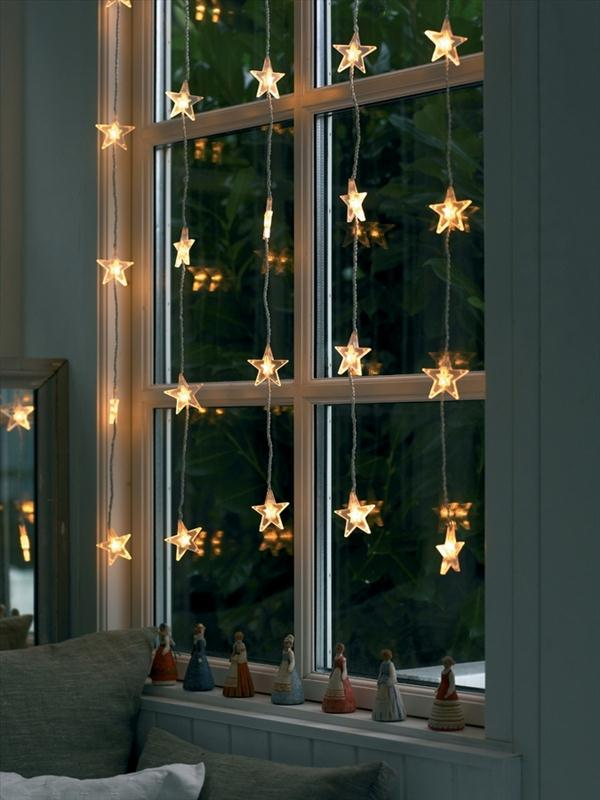 Christmas window decoration ideas with garlands, candles and displays