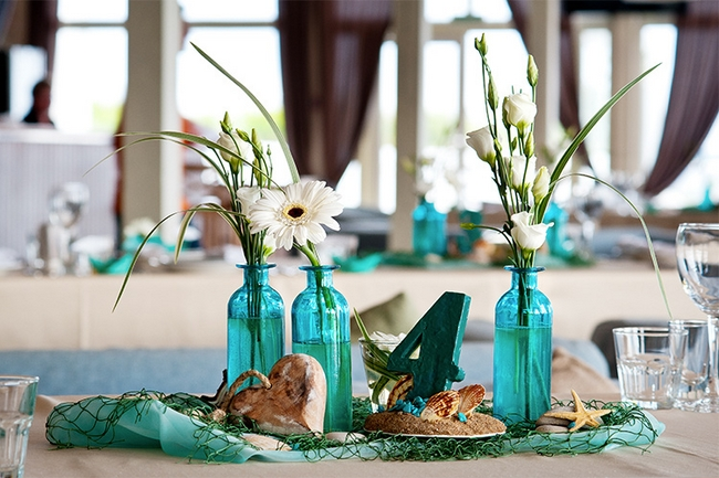 beach-themed-wedding-table-decor-centerpieces-turquoise-vases-white-flowers