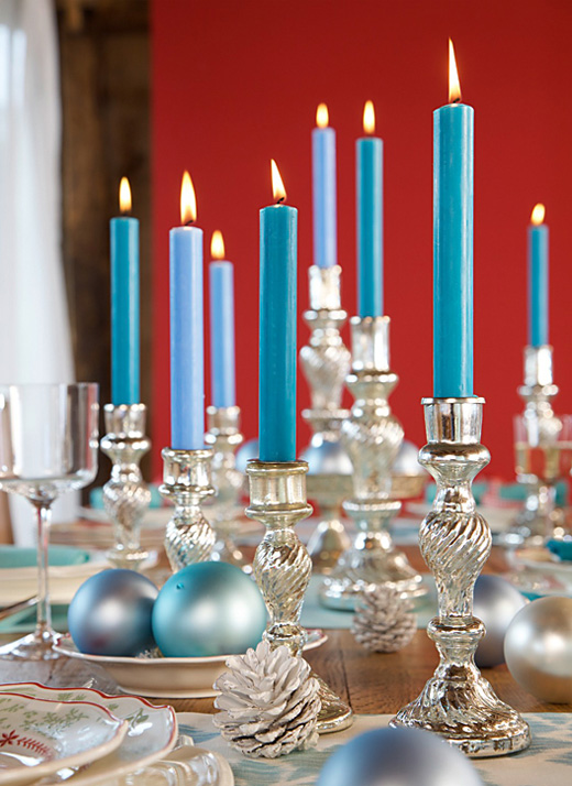 christmas table decoration blue candles in silver candlesticks festive table setting white painted cones