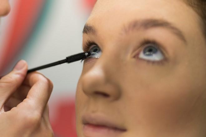 applying mascara blue eyes