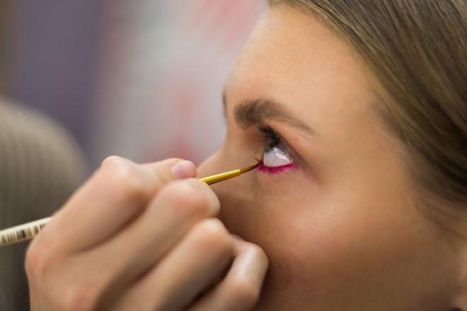 applying pink eyeliner thin brush