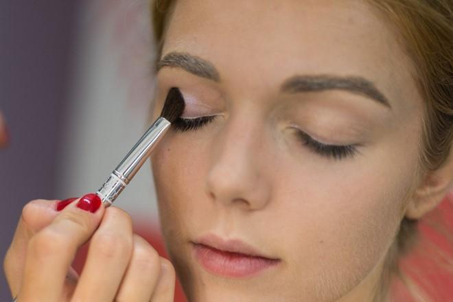 applying white eyeshadow using brush