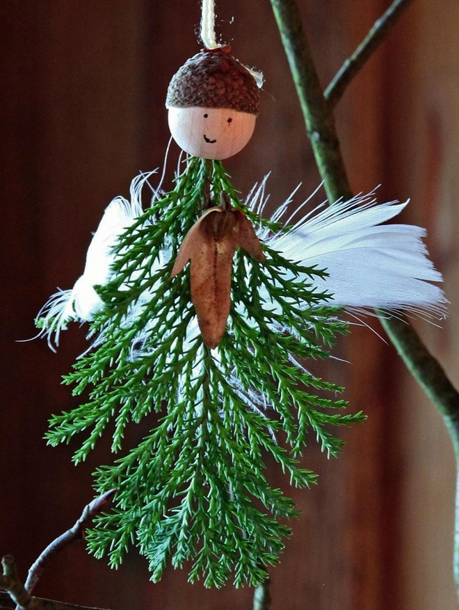 cute christmas angel ornaments with juniper twig and white feathers wings