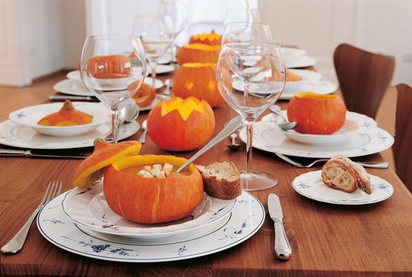 pumpkin soup served in hollow out pumpkins attractive table setting