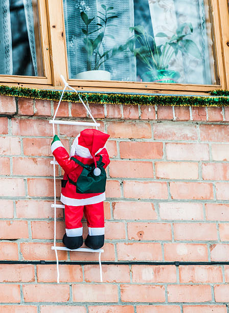 Outdoor Christmas Decoration Santa hanging on a ladder house facade